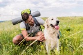 Fotografie traveler with backpack and dog sitting on green meadow