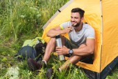 Fényképek smiling traveler sitting in yellow tent with backpack and drinking coffee from thermos