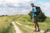 Fotografie hezký tramp s batohem na zelené louce