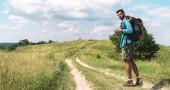 Fotografie cestovatel s batohem na cestu na zelené louce