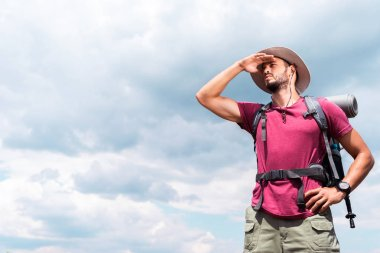 handsome tourist in hat looking away, with cloudy sky background