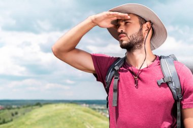 traveler in hat with backpack looking away on summer meadow