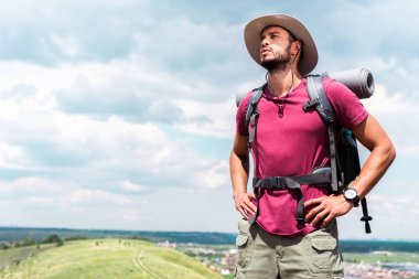 handsome hiker in hat with backpack and tourist mat