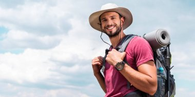 smiling traveler in hat with backpack and tourist mat, with cloudy sky background