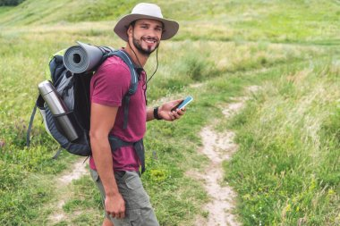 traveler with backpack using smartphone on summer meadow