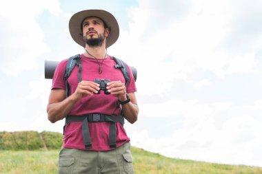 Traveler in hat with backpack holding binoculars stock vector