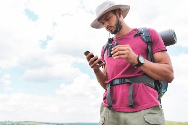 male traveler with backpack and binoculars using smartphone