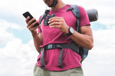 cropped view of tourist with backpack and binoculars using smartphone