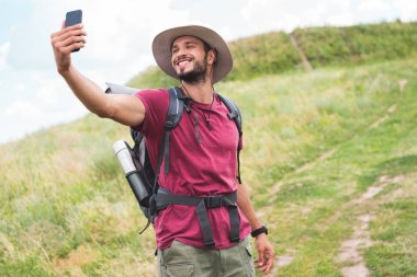 Traveler with backpack taking selfie on smartphone on summer meadow stock vector
