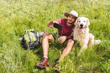 traveler in hat taking selfie on smartphone with dog on summer meadow