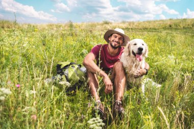 male traveler sitting with dog on green summer meadow