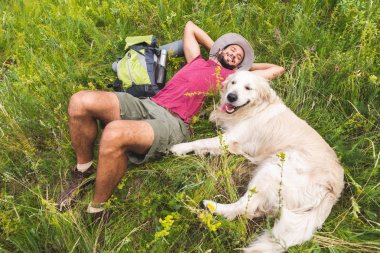 top view of smiling traveler and golden retriever dog lying on green grass with backpack