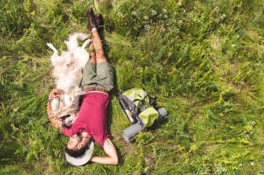 top view of tourist and dog lying on green grass with backpack