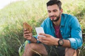 Fotografie traveler using smartphone and eating sandwich on summer meadow