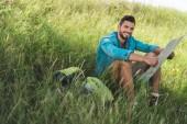 Fotografie usmíval se cestující sedí na zelené trávě s batohem a mapa