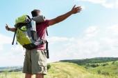 Fotografie Tourist mit Rucksack stehend mit ausgestreckten Händen auf sommerwiese mit bewölktem Himmel