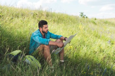 traveler sitting on green grass with backpack and looking at map