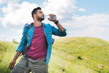 handsome traveler with backpack drinking water on summer meadow