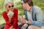 smiling couple in sunglasses eating sandwiches at picnic in park