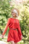 Fotografie smiling attractive girl in red dress and straw hat looking away in park