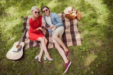 high angle view of couple lying on blanket in park with glasses of wine