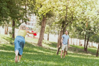 young couple playing frisbee in park in summer