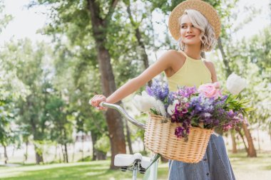 attractive girl holding bike with basket of flowers in park