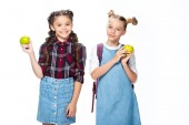 usmívající se školáci drží jablka a při pohledu na fotoaparát izolované na bílém