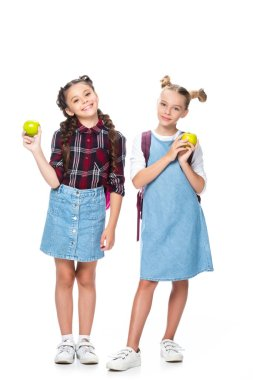 schoolchildren holding apples and looking at camera isolated on white