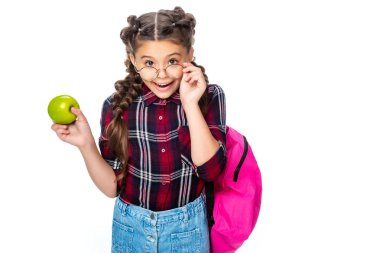 schoolchild holding ripe apple and looking at camera above glasses isolated on white