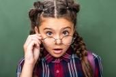 překvapený školák při pohledu na fotoaparát nad brýlemi poblíž tabule