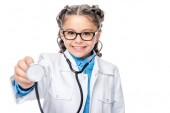 schoolchild in costume of doctor examining with stethoscope isolated on white