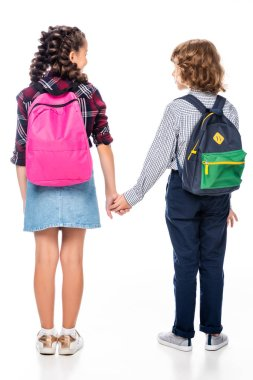 back view of classmates with backpacks holding hands isolated on white