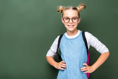 smiling schoolchild in glasses posing near blackboard