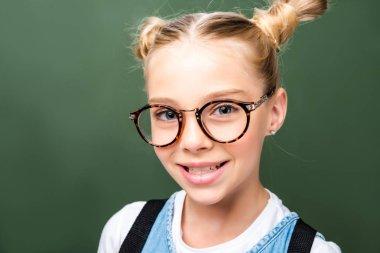 portrait of adorable schoolchild in glasses looking at camera near blackboard