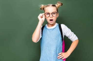 shocked schoolchild touching glasses and looking at camera near blackboard