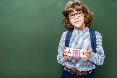 schoolboy holding wooden cubes with word art near blackboard