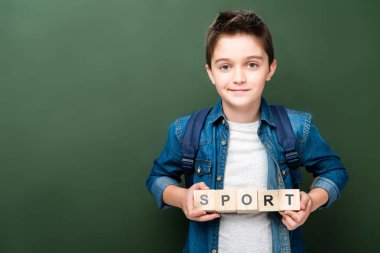 schoolboy holding wooden cubes with word sport near blackboard
