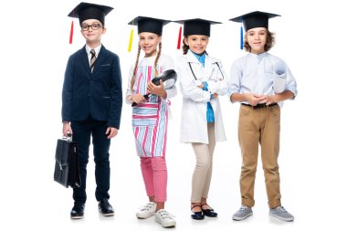 schoolchildren in costumes of different professions and graduation caps looking at camera isolated on white