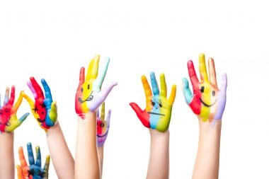 cropped image of schoolchildren showing painted hands with smiley icons isolated on white