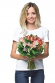 Fotografie smiling attractive girl holding bouquet of flowers and looking at camera isolated on white