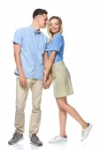 smiling couple in blue shirts holding hands isolated on white