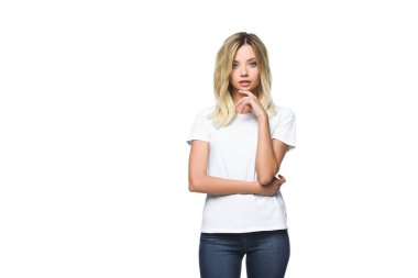 attractive pensive girl in white shirt touching chin and looking at camera isolated on white