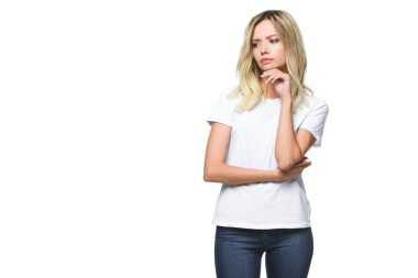 attractive pensive girl in white shirt and jeans looking away isolated on white