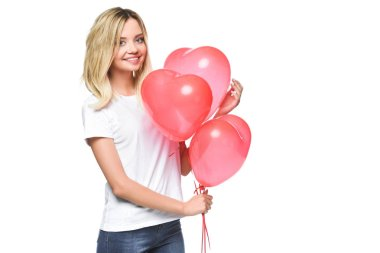 smiling attractive girl in white shirt holding bundle of heart shaped balloons isolated on white