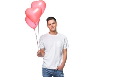 smiling man standing with bundle of heart shaped balloons isolated on white