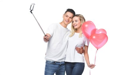 couple with balloons taking photo with smartphone and selfie stick isolated on white