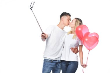 couple kissing and taking photo with smartphone and selfie stick isolated on white