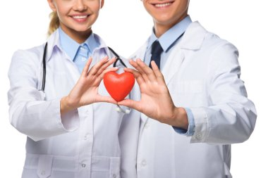 cropped view of two doctors in white coats holding red heart, isolated on white