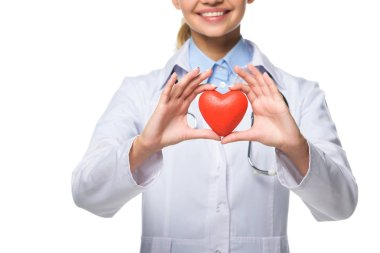 Cropped view of young doctor in white coat holding red heart, isolated on white stock vector